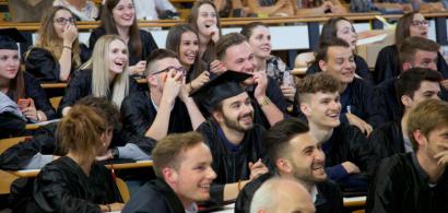 Des étudiants souriants en toge et toques de diplômés dans un amphithéâtre