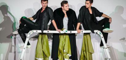 Scène de théâtre : trois jeunes hommes discutent autour d'une échelle.