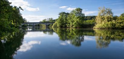 Une vue de l'Ognon avec des arbres et un pont.