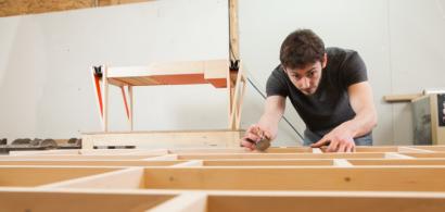Samuel Hélias penché sur une réalisation en bois dans son atelier.