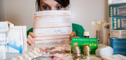 Une jeune femme derrière une feuille de soins regarde une pile de médicaments et d'argent.