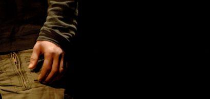 Gros plan sur une main, un bras, un pull et un jean sur fond noir.