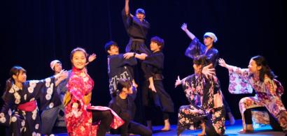 Un groupe de japonais en costume exécute une danse.