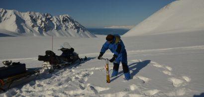 Un homme en train de faire un carottage de glace
