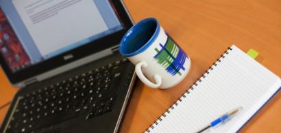 Un ordinateur portable, un mug et un cahier