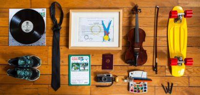 Plusieurs objets (violon, chaussures de sport, passeport, cravate, skate-board, pinceaux et peinture, appareil photo...) encadrent un diplôme.