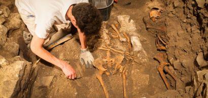 Un étudiant fouille le sol. On voit deux squelettes.