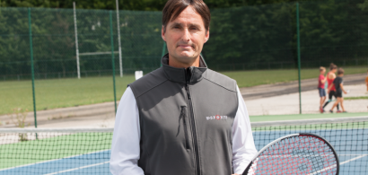 Vincent Peseux sur un court de tennis avec une raquette. Des enfants en arrière plan