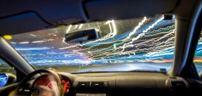 Un pare-brise de voiture vu de l'intérieur avec des lignes lumineuses colorées sur la route.