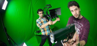 Un jeune homme tient une caméra pointée sur un autre qui tient une arme. En arrière plan, un fond vert et des éclairages de cinéma.