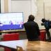 Un homme de dos avec une caméra qui regarde un grand écran sur lequel on voit des images en trois dimensions.