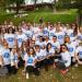 Un groupe d'étudiants qui portent tous le même tee shirt et des lunettes de soleil colorées.