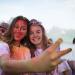 Deux étudiantes couvertes de poudre colorée font un selfie.