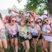 Un groupe d'étudiants avec des lunettes de soleil et couverts de poudre colorée posent en groupe.