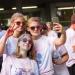 Quatre étudiantes couvertes de poudre colorée font un selfie.