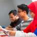 Deux étudiants et une étudiante malaisienne souriants.