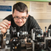 John Dudley en train de manipuler un banc optique