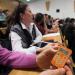 Dans un amphithéâtre, une personne montre un petit boitier numérique orange qui ressemble à une calculatrice.