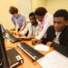 Quatre étudiants travaillant en groupe devant des ordinateurs