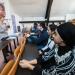 Une femme en train de parler à un groupe d'étudiants dans un amphithéâtre.