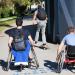 Deux personnes en fauteuil roulant de dos, un jeune homme en skateboard devant