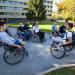 Un groupe d'étudiants en fauteuil roulant en train de discuter en extérieur.