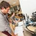 Un étudiant et une étudiante devant une machine d'encapsulage de bocaux