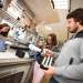 Trois étudiants en travaux pratiques autour d'une machine de production industrielle.