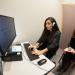 Expérience en psychologie dans un box : une étudiante avec un casque devant un ordinateur et une autre en retrait qui prend des notes.