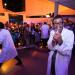 Un homme avec des lunettes et une blouse blanche montre une seringue à l'objectif en grimaçant. Derrière lui, d'autres personnes en blouse blanche face au public, amusé, avec de nombreux enfants au premier plan.