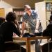 Un homme debout appuyé sur une table où des gens réfléchissent dans une bibliothèque.