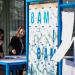 Un meuble mobile, des affiches BAM ! et des personnes souriantes autour du plan de travail.