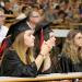 Deux jeunes filles avec toques et chapeaux de diplômés dans un amphithéâtre.