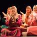 Des étudiantes malaisiennes en costume traditionnel en train de taper des mains assises sur une scène.