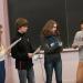 Un groupe de lycéens, garçons et filles, tenant des feuilles devant un tableau. L'un parle dans un micro.