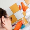 Une jeune femme de dos en blouse et gants oranges manipule une pipette.